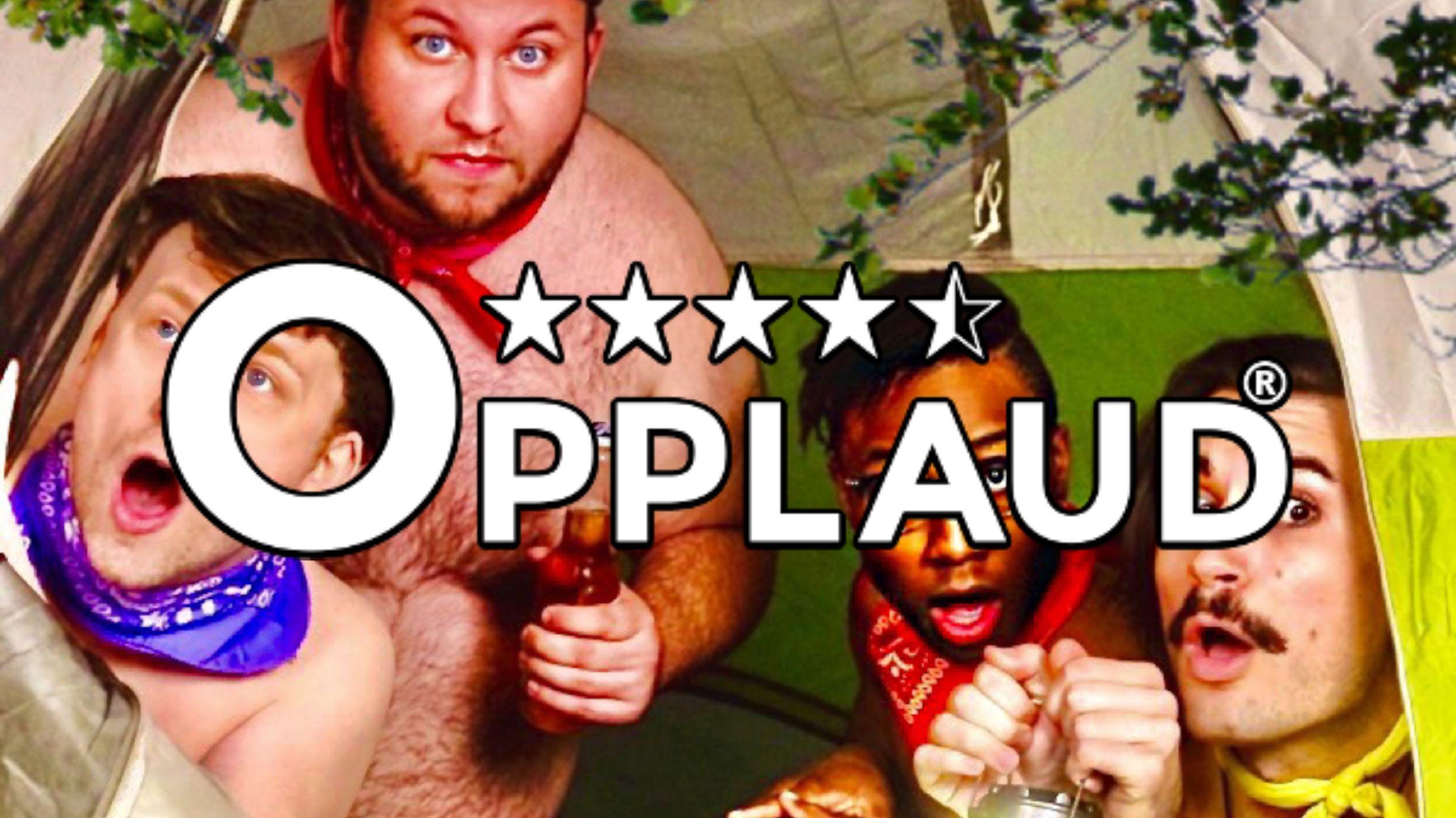 Four men (one shirtless) look out of a tent with their mouths open in surprise